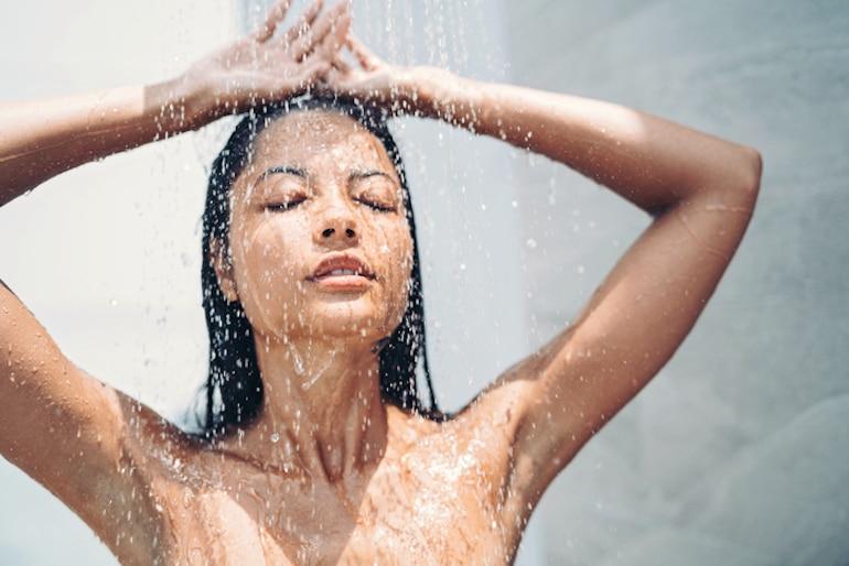 Mujer con hermoso cabello y piel tomando una ducha