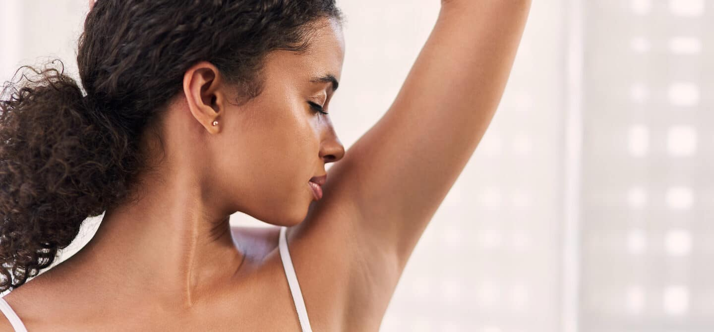 Woman smelling her armpit trying to determine the causes of body odor