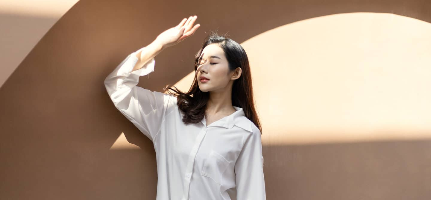 Woman blocking sunlight with her hand, wondering if sunscreen causes acne
