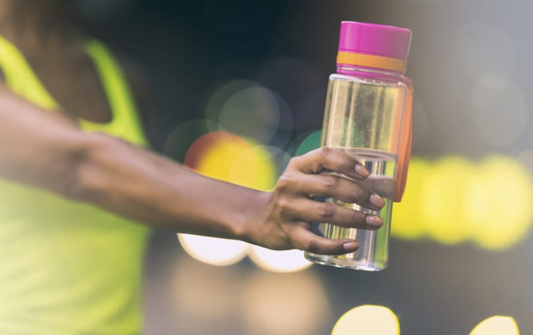 Athletic woman holding a water bottle, showing off her strong nails