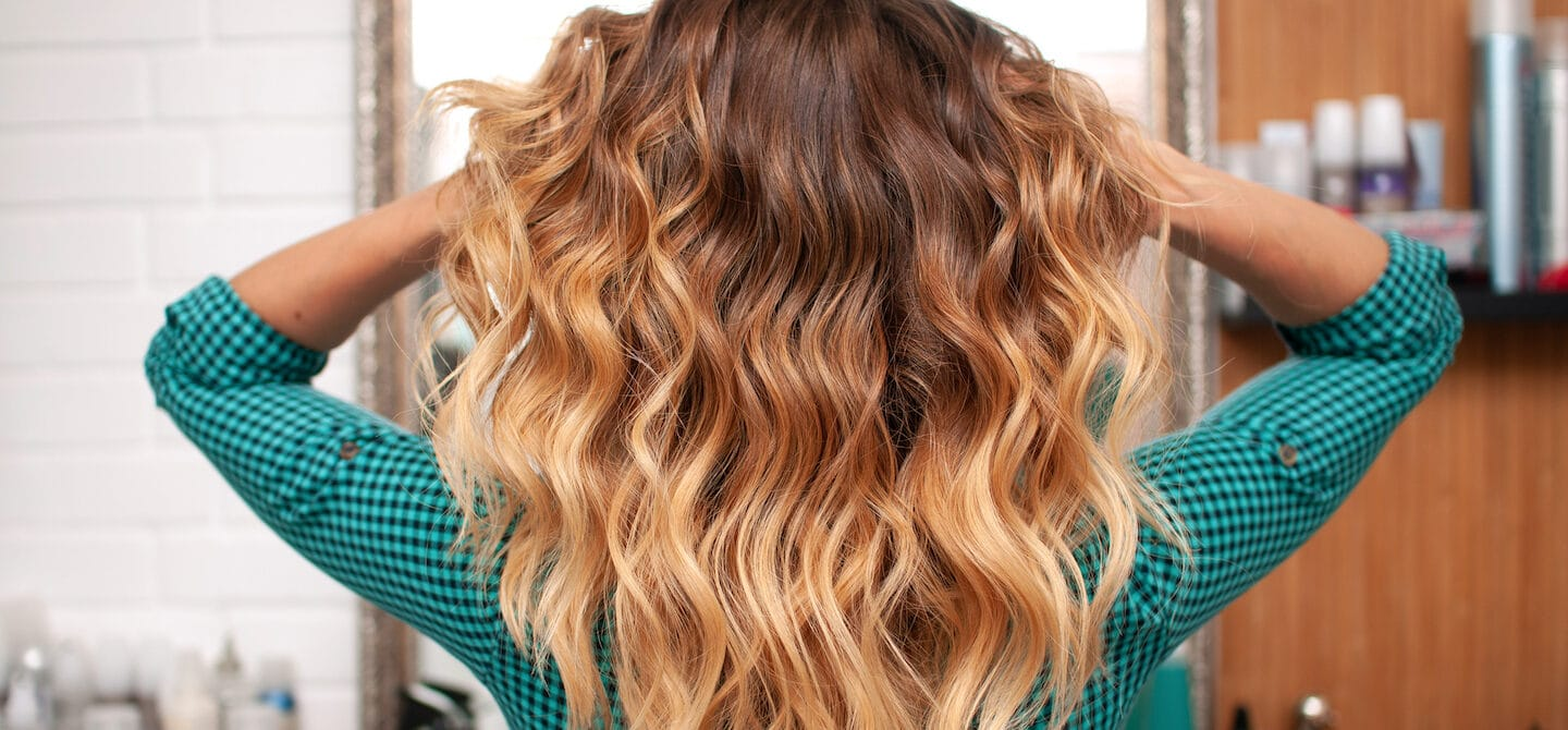 Woman with perfect beach waves running hands through her hair