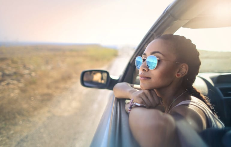 Woman with braids looking out of car window