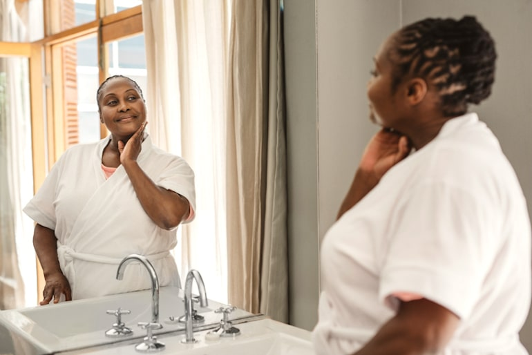 Black woman combating hyperpigmentation thats to PHA exfoliants