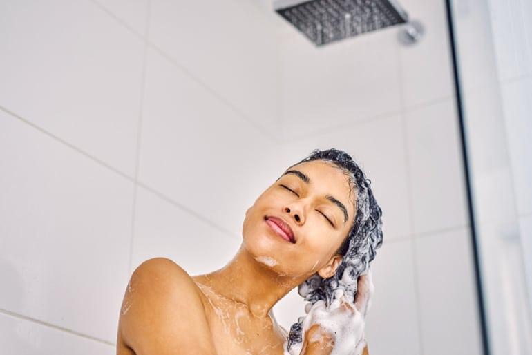 Woman washing hair under shower head filter