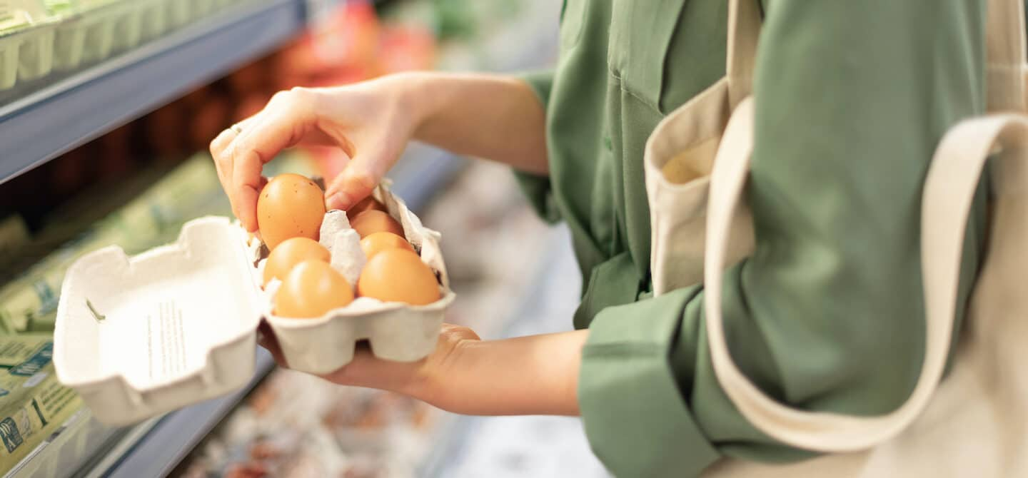 Woman at supermarket holding pasture-raised eggs, the best eggs to buy based on nutritional content and value