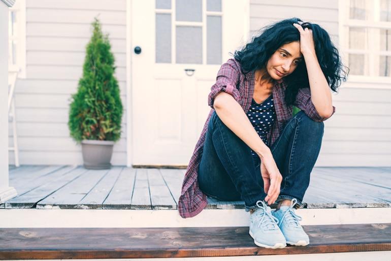 Postmenopausal women sitting in discomfort on stoop