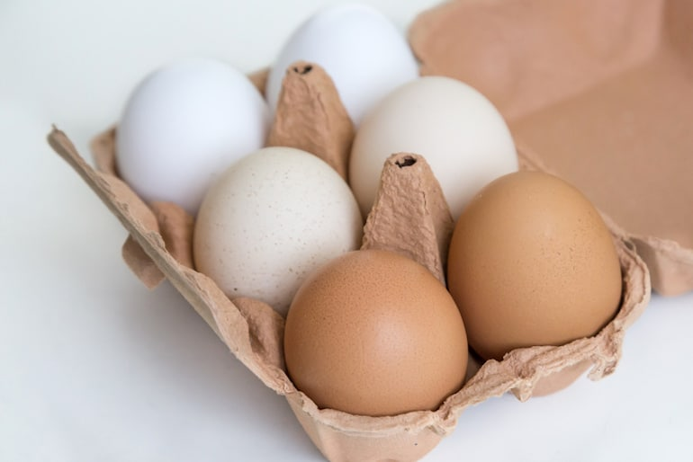 White, tan, and brown eggs in a carton