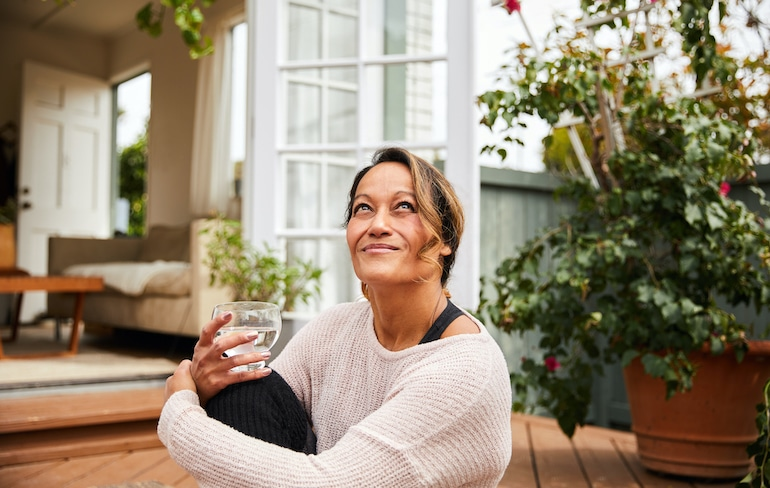 Menopausal woman sitting outside hydrating to help with vaginal dryness