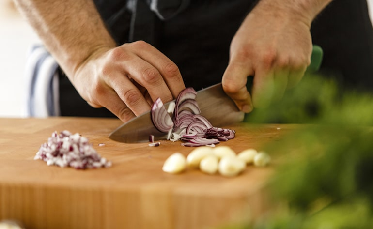 Man slicing onion and garlic, both of which are foods that cause body odor