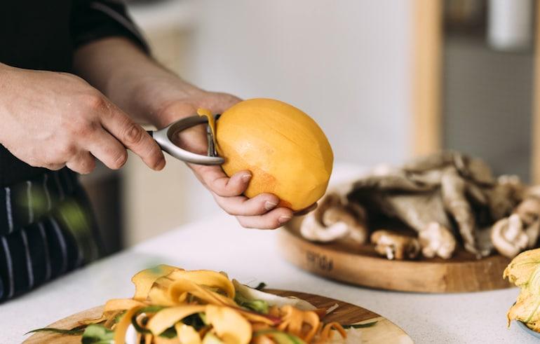 Hombre pelando mango para comer por sus beneficios para la salud