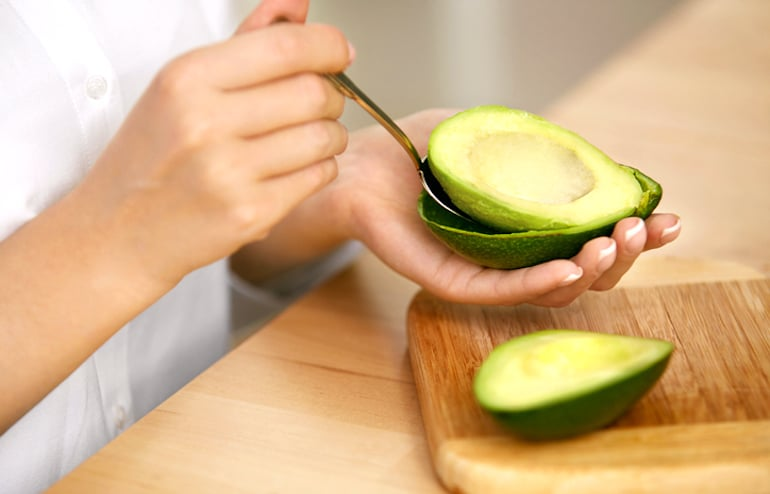 Woman scooping avocado from skin to make a vegan easy gazpacho recipe