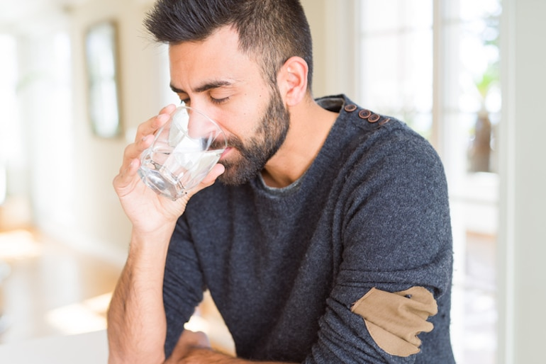 Man drinking filtered tap water to stay hydrated and healthy