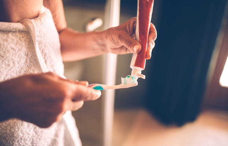 Woman applying toothpaste to remove stains and discoloration