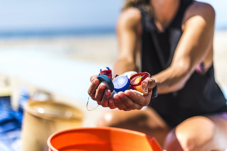 Woman holding bottle caps that would end up as plastic pollution in the ocean