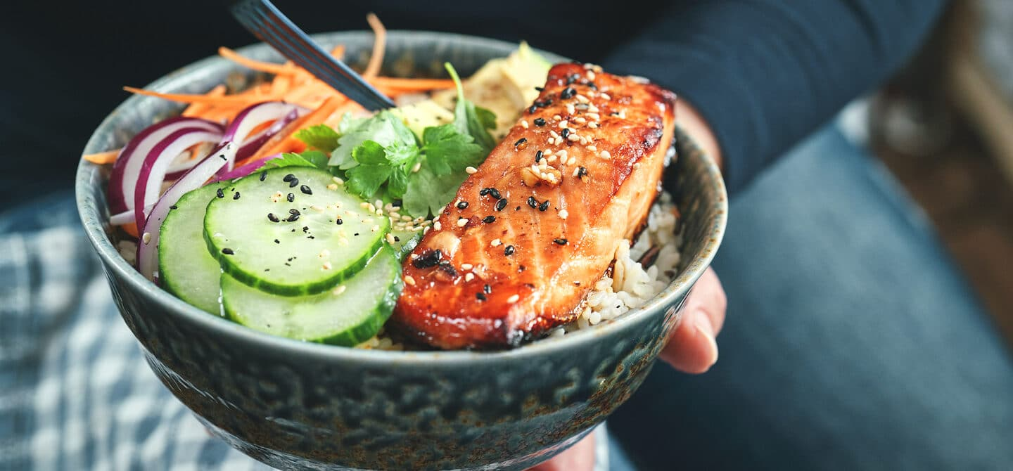 Person eating a salmon, one of the healthiest fish to eat, in a poke bowl