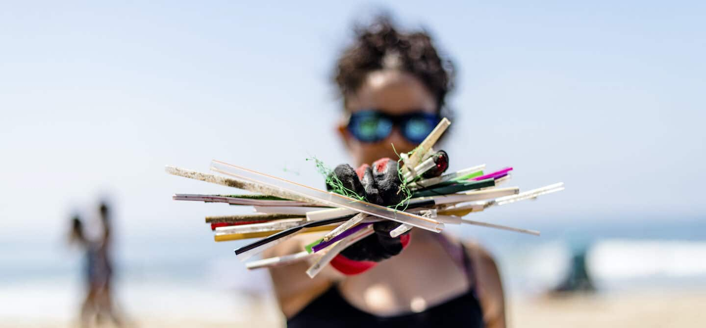 Woman holding up plastic straws on a Surfrider Foundation beach cleanup to protect ocean