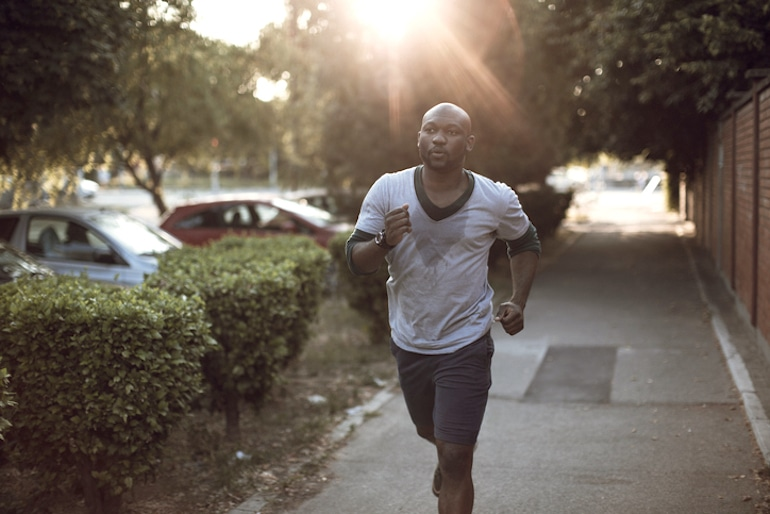 Man running on street sweating through his shirt