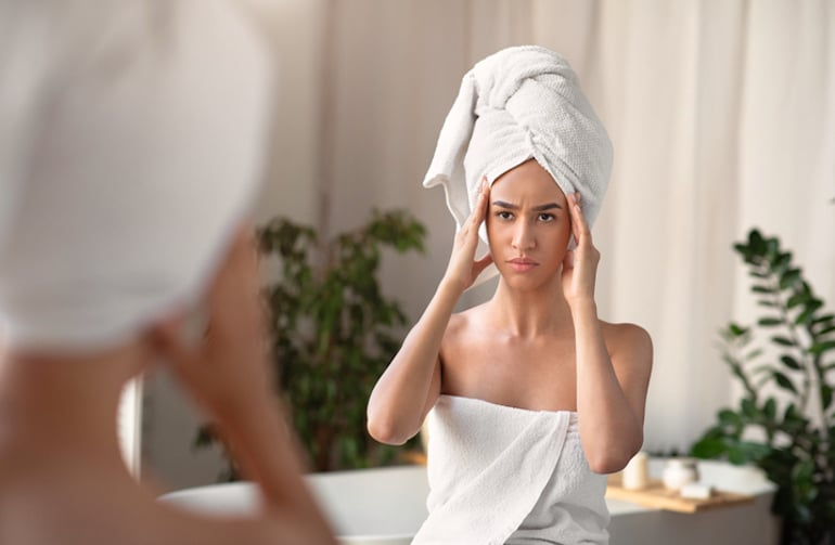 Woman out of shower looking at collagen loss via wrinkles
