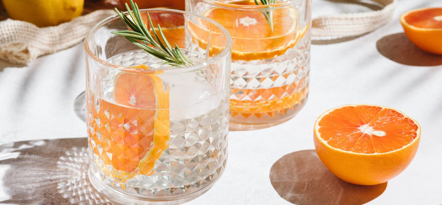 Healthiest hard seltzer in glasses with citrus fruits