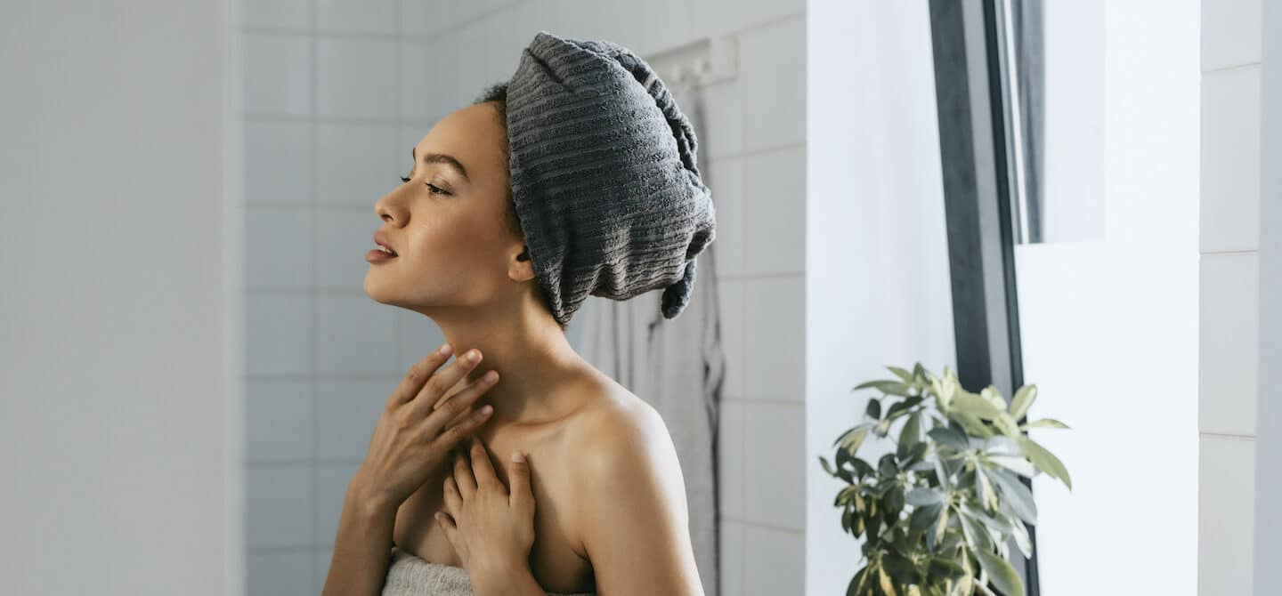 Woman out of shower looking at her complexion after using probiotic skincare