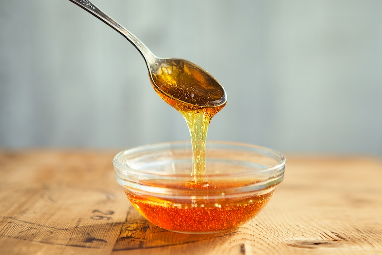 Honey dripping from spoon in the cup