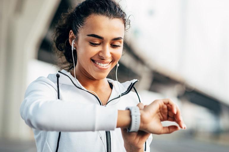 زنی که به ساعت ورزش خود نگاه می کند