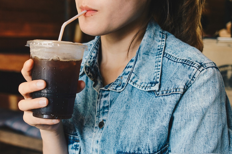 woman sipping iced coffee